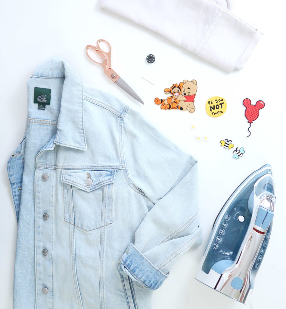 All the supplies needed for this jacket diy including sewing kit, iron, patches and denim jacket